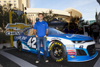 Kyle Larson posing in front of his NASCAR #42 car
