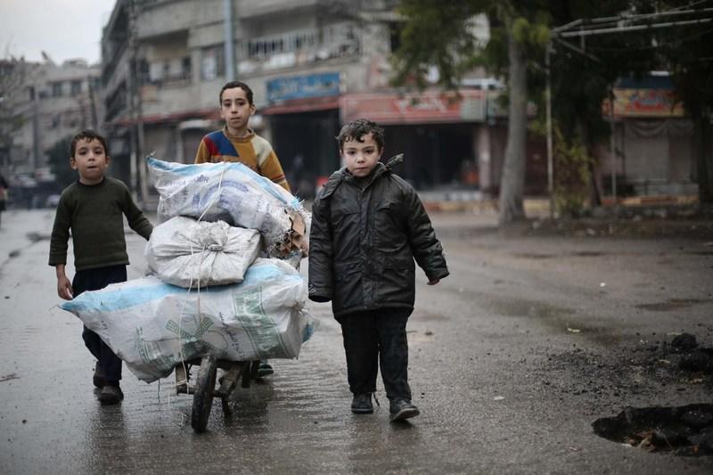 Des enfants dans la zone assiégée de la Ghouta orientale transportent du bois de chauffage pour leur famille. © UNICEF/UN0127391/Al Shami (Groupe CNW/UNICEF Canada)
