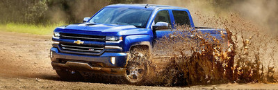 Blue Chevrolet Silverado 1500 driving splashing up a wave of mud.
