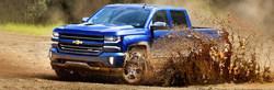 Blue Chevrolet Silverado 1500 driving splashing up a wave of mud.