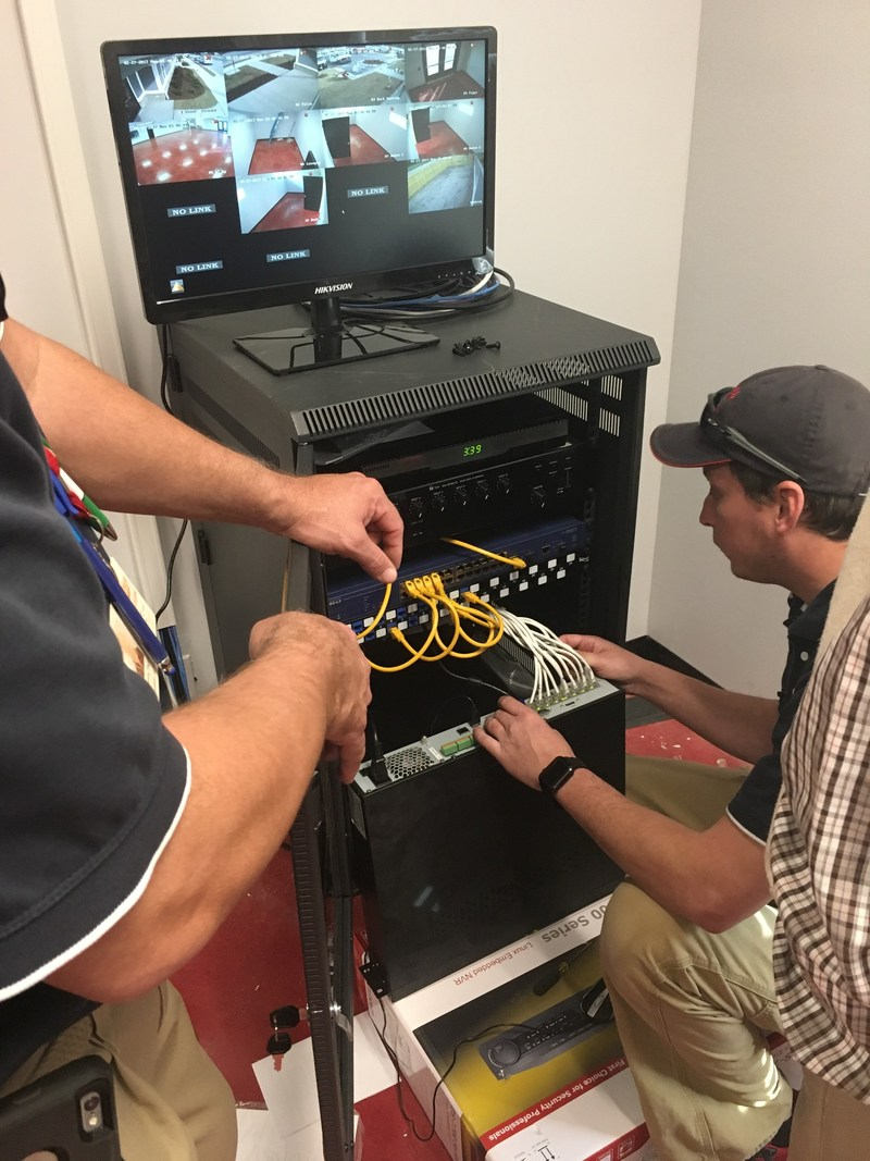 The Holmes Security crew at work: Tommy Page assists technician James Tilley in setting up the Hikvision security hardware at Operation INASMUCH. Here, Tilley kneels to connect camera cables to the NVR.