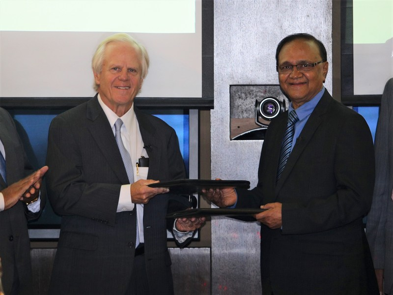 HelpMeSee chairman James Tyler Ueltschi (left) exchanges signed agreements with ISMSICS chairman Dr. Amulya Sahu (right) during a ceremony in Chennai, India.