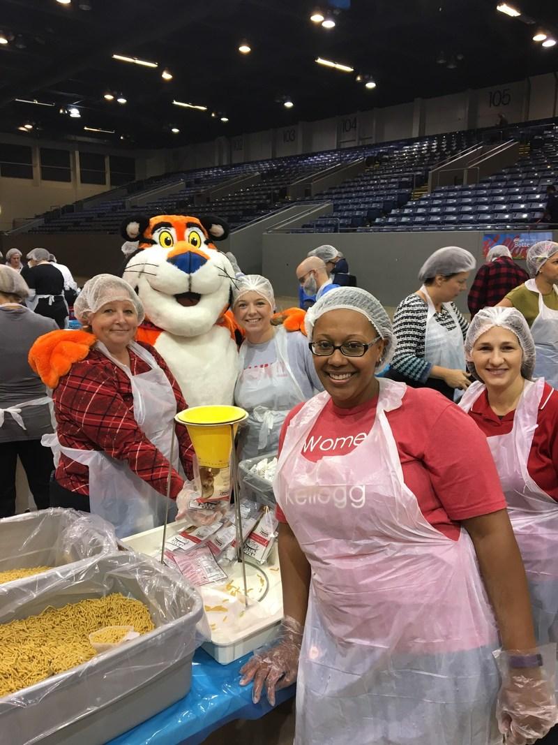 Members of Women of Kellogg Volunteering to Pack Food