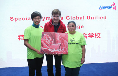 Two representatives from Amway's volunteer team and Sunshine Home present the completed oil painting to senior director of Special Olympics' global youth program Soren Palumbo