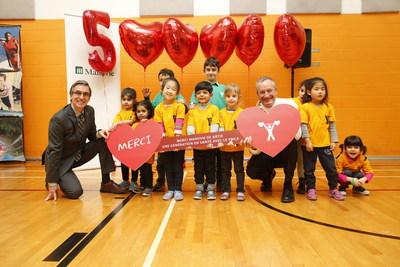 De gauche à droite : M. Stéphane Vaillancourt, président-directeur général des YMCA du Québec, M. Richard Payette, président et chef de la direction de Manuvie Québec, entourés d'enfants du YMCA. (Groupe CNW/YMCA)