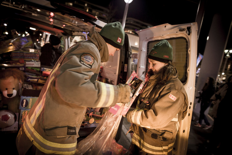 """Toronto Fire Fighters unload cargo vans full of toys collected at Mercedes-Benz dealerships across the GTA. A fleet of Mercedes-Benz Vans delivered the toys to the official kick-off for the Fire Fighters Toy Drive at CF Shops at Don Mills. Mercedes-Benz Toronto Retail Group has supported the Toronto Fire Fighters Toy Drive for four years. """"We are proud to work with this charitable organization that has made a difference in the lives of thousands of children and their families over the years,"""" says Philipp von Witzendorff, Vice President and Head of Toronto Retail Operations, Mercedes-Benz Canada. (CNW Group/Mercedes-Benz Canada Inc.)"""