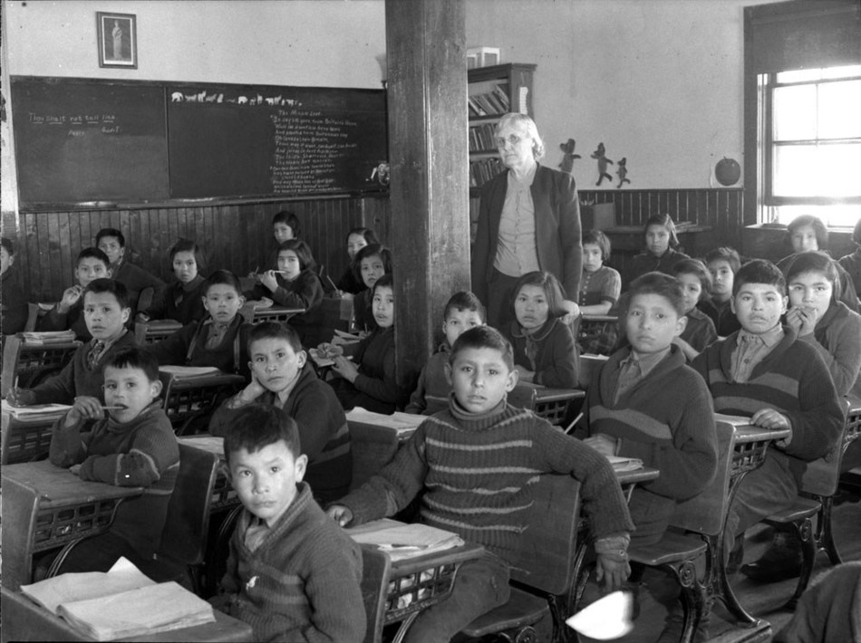 Cree students at their desks with their teacher in a classroom, All Saints Indian Residential School, Lac La Ronge, Saskatchewan, March 1945 (CNW Group/Royal Canadian Geographical Society)
