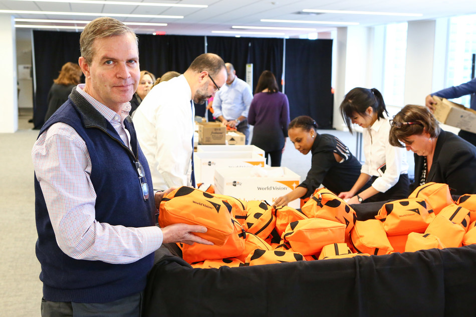 Art Steinmetz, Chairman and CEO of OppenheimerFunds, assembles hurricane recovery kits during an employee volunteering event in partnership with World Vision.