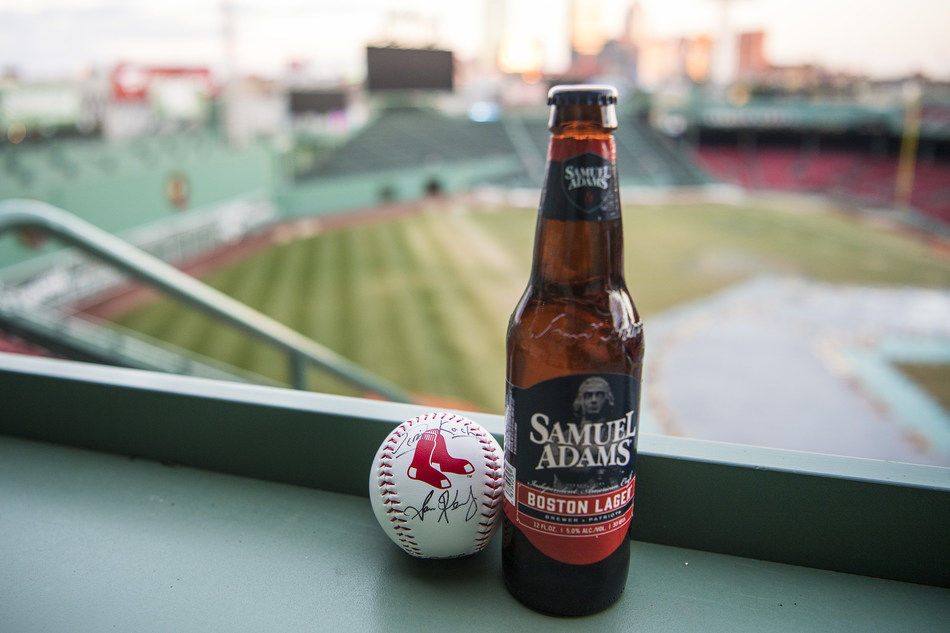 December 7, 2017, Boston, MA: A baseball autographed by Samuel Adams Founder Jim Koch and Boston Red Sox President and CEO Sam Kennedy is displayed next to a bottle of beer during the announcement of a partnership at Fenway Park in Boston, Massachusetts Thursday, December 7, 2017.  (Photo by Billie Weiss/Boston Red Sox)