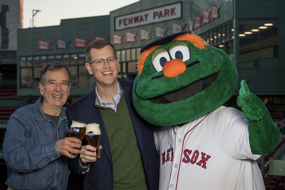 December 7, 2017, Boston, MA: Samuel Adams Founder Jim Koch and Boston Red Sox President and CEO Sam Kennedy pose for a photograph with Boston Red Sox mascot Wally the Green Monster during the announcement of a partnership at Fenway Park in Boston, Massachusetts Thursday, December 7, 2017.  (Photo by Billie Weiss/Boston Red Sox)
