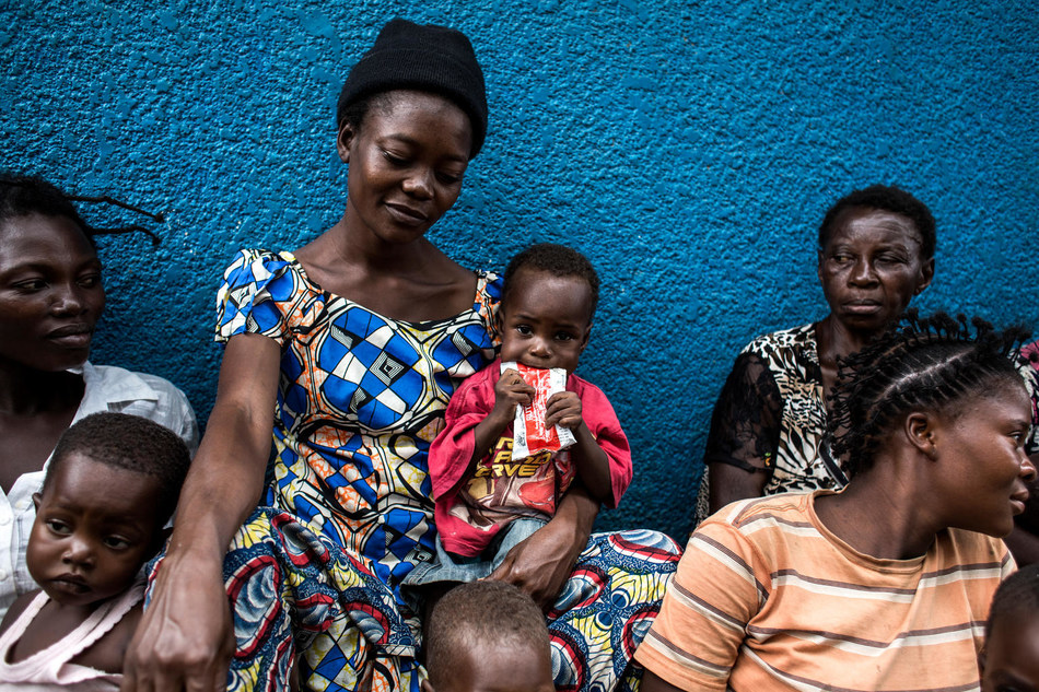 A young boy eats a packet of plumpy'nut, which is used for the treatment of severe acute malnutrition, as he sits with his mother outside a UNICEF supported clinic in, Kananga. © UNICEF/UN0126955/Wessels (CNW Group/UNICEF Canada)