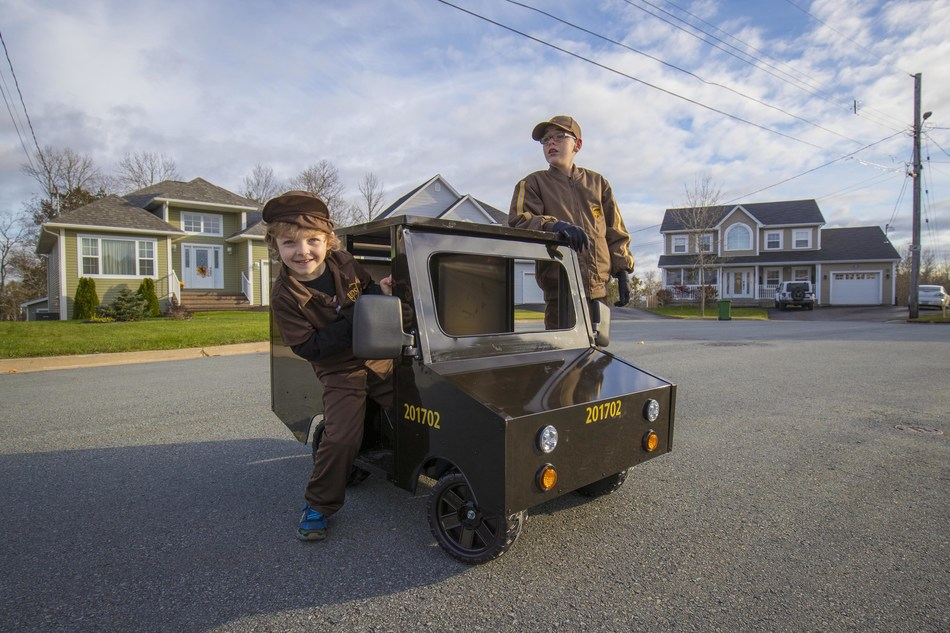 Pictured: Cooper (left) and Jax (right) take Cooper's new mini UPS® delivery truck out for a drive. (CNW Group/UPS Canada Ltd.)