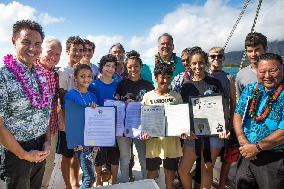 Hawaii students hold proclamations setting a 100% renewable transportation target of 2045 while surrounded by Honolulu Mayor Kirk Caldwell, Maui Mayor Alan Arakawa, Kauai Mayor Bernard Carvalho, and others aboard the traditional Hawaiian voyaging canoe Hokulea on December 12, 2017.