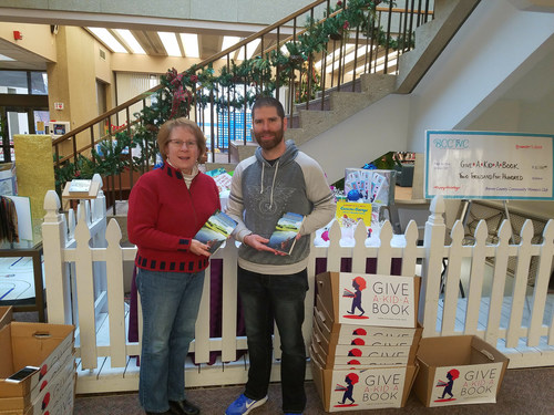 """Cory Groshek, author of children's book """"Breaking Away: Book One of the Rabylon Series"""" and founder of Manifestation Machine, with Meg Deem of the Friends of the Brown County Library, who is accepting copies of """"Breaking Away"""" on behalf of the annual Give a Kid a Book campaign at the Central Library in downtown Green Bay, Wisconsin."""