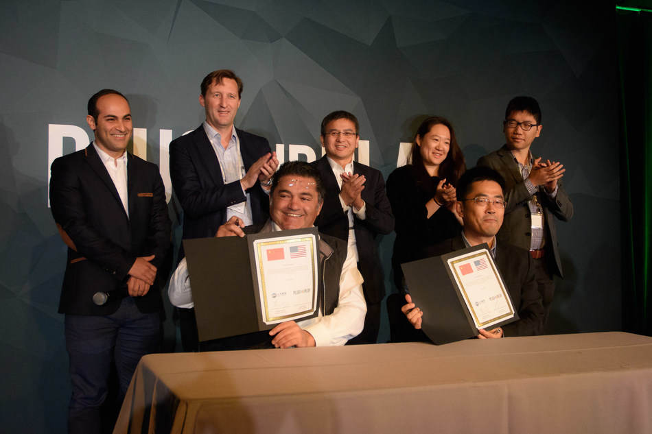 Maxwell Huang, President at SAIC Venture Capital (right front), and Saeed Amidi, CEO and Founder of Plug and Play (left front) formalize their partnership.
