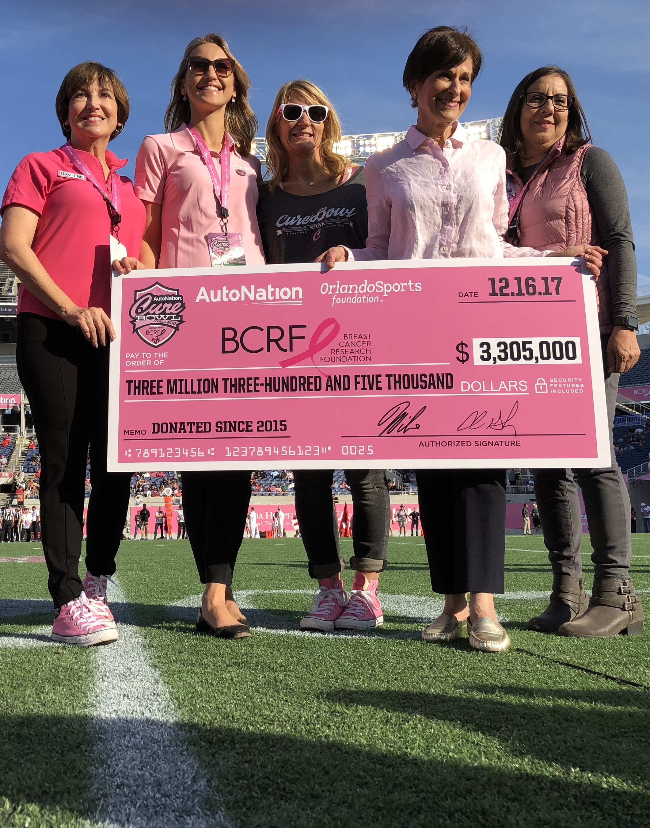 AutoNation & Orlando Sports Foundation present check to BCRF at the AutoNation Cure Bowl.