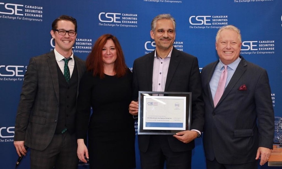 Tejinder Basi of BIG accepts the listing certificate from the CSE, presented by James Black (left), Anna Serin, and Richard Carleton (right) (CNW Group/Big Blockchain Intelligence group inc)