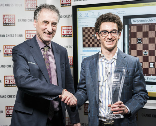 American Grandmaster Fabiano Caruana (right), the No. 2 rated player in the world, accepts the 2017 London Chess Classic trophy.