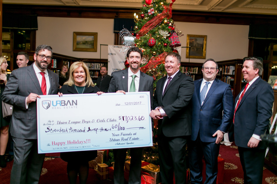 Urban Real Estate partners present a check for more than $17,000 to the Union League Boys & Girls Clubs during the brokerage's annual holiday event.