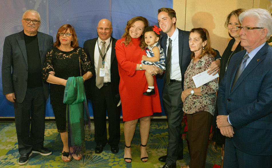 MDAD's Joe Napoli (third from left) and GMVCB's Bill Talbert (far right) join Rossi and Consuegra's (center) families for a picture at MIA's Rewards and Recognition Year-End Gala on December 14.