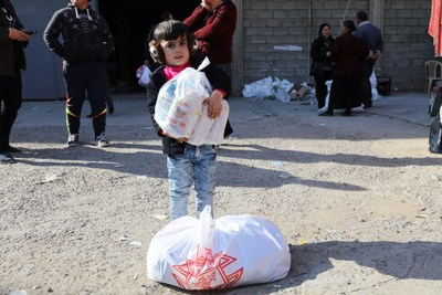 "Little child manages a portion of the ""Christmas basket"" given to persecuted Christians in Iraq by the Knights of Columbus."