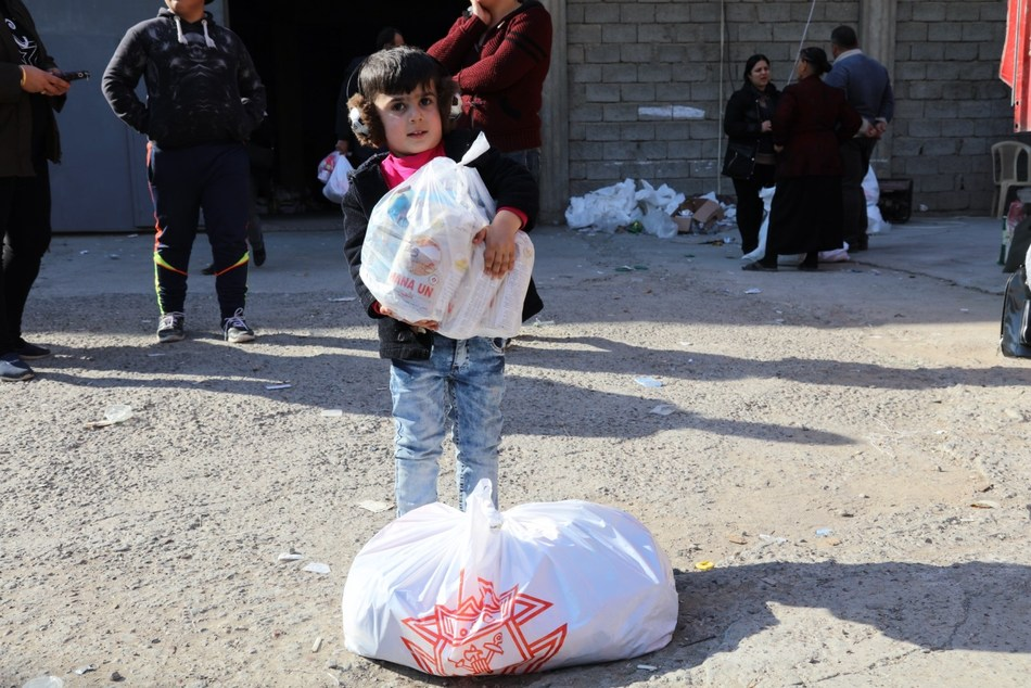 """Little child manages a portion of the """"Christmas basket"""" given to persecuted Christians in Iraq by the Knights of Columbus."""
