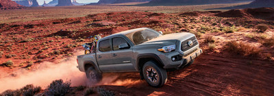 2018 Toyota Tacoma driving off-road through sand dunes.