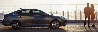 View of a couple standing arm in arm next to the 2018 Hyundai Sonata at dusk.