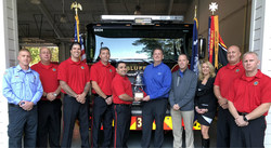 Members of the Bluffton Township Fire District, Hilton Head Honda and Mercedes-Benz of Hilton Head display a new donated fire bell.