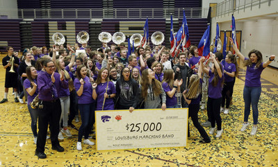 The Louisburg High School marching band members react Nov. 28 after receiving a $25,000 check. Cheerios, as part of its Moments of Good program with Walmart, surprised the band leader John Cisetti (front left) and his band at an all-school assembly to help them meet their fundraising goal for the band's first-ever trip to the Rose Parade.