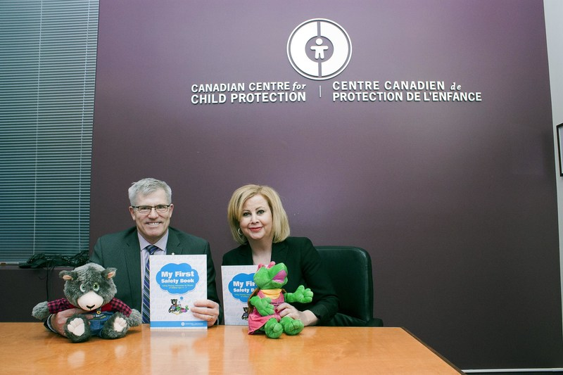 Commissioner Vince Hawkes, Ontario Provincial Police and Lianna McDonald, Executive Director for the Canadian Centre for Child Protection with puppets and My First Safety Book, a new safety tool that helps children aged four to seven develop personal safety skills. (CNW Group/Ontario Provincial Police)