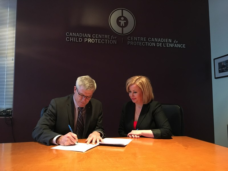 Commissioner Vince Hawkes, Ontario Provincial Police and Lianna McDonald, Executive Director for the Canadian Centre for Child Protection sign an important agreement to enhance the safety of children and youth in Ontario. (CNW Group/Ontario Provincial Police)