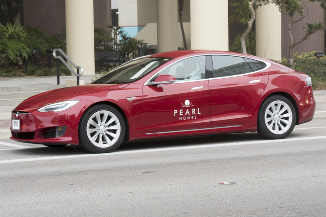 The red Pearl Homes Tesla Model S vehicle parked out front of the Land Use hearing.