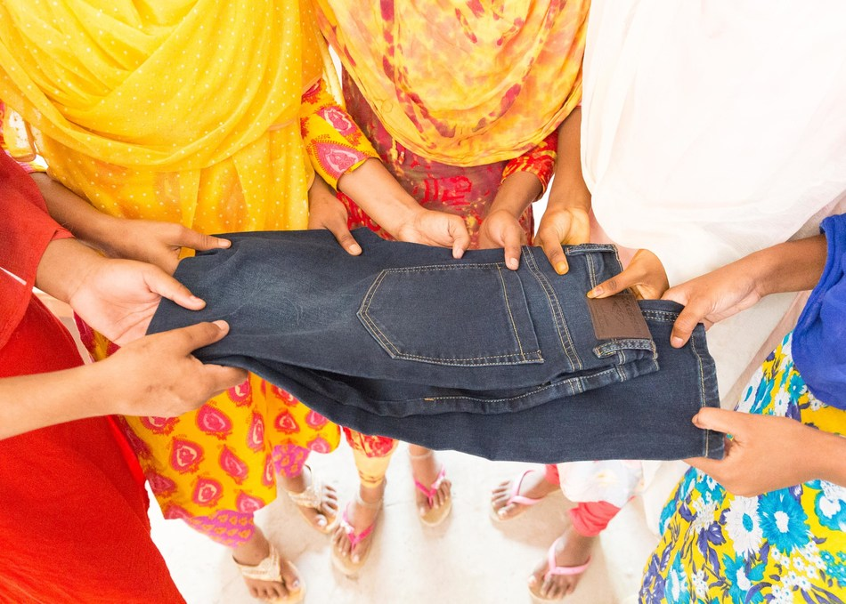 Exploited child factory workers in Bangladesh hold a pair of jeans. More than 73-million children are engaged in dirty, dangerous and degrading work around the world, according to the International Labour Organization. Photo/World Vision. (CNW Group/World Vision Canada)