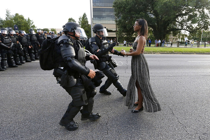 Protester Ieshia Evans stands firm as Louisiana State troopers in riot gear rush toward her during a 2016 Black Lives Matter protest in Baton Rouge, La. She was arrested for obstructing a highway. The photo went viral and became a symbol of the continuing struggle for civil rights for all Americans. Credit: Jonathan Bachman, Reuters