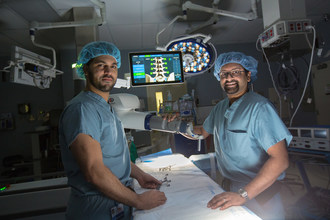 Henry Ford Allegiance Health neurosurgeons Azam Basheer, MD, (left) and Amritraj Loganathan, MD, with the ExcelciusGPS robot.