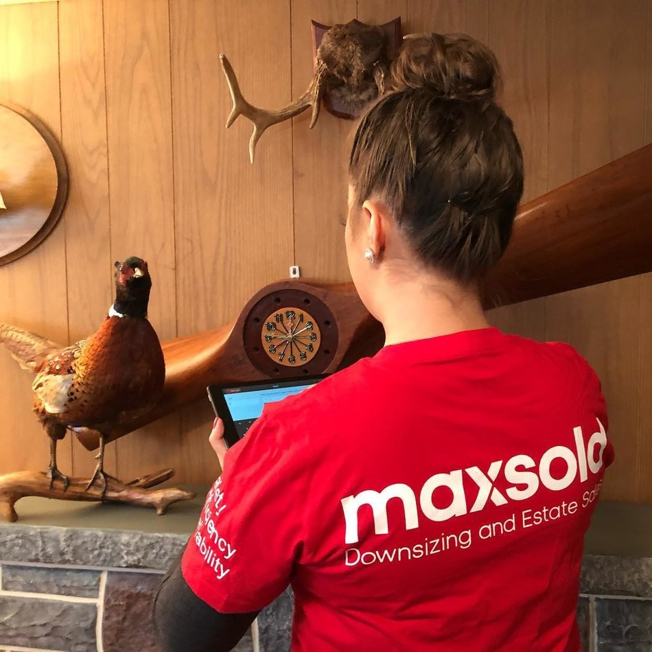 MaxSold staff cataloging items for an online estate sale auction.