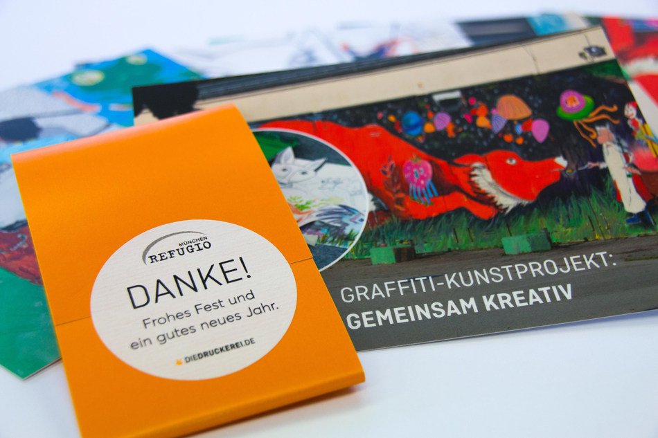 """The 2017 annual edition for sponsors and donors of Refugio Munchen comprises seven postcards with banderole and label. The postcards depict sections of a mural painting created during the """"on the road"""" art project. It decorates the wall of the former Bavarian barracks, today a collective accommodation centre for refugees. The set of postcards was produced by Onlineprinters. Copyright: Onlineprinters GmbH/ Sabine Mayer, Refugio Munchen (PRNewsfoto/Onlineprinters GmbH)"""