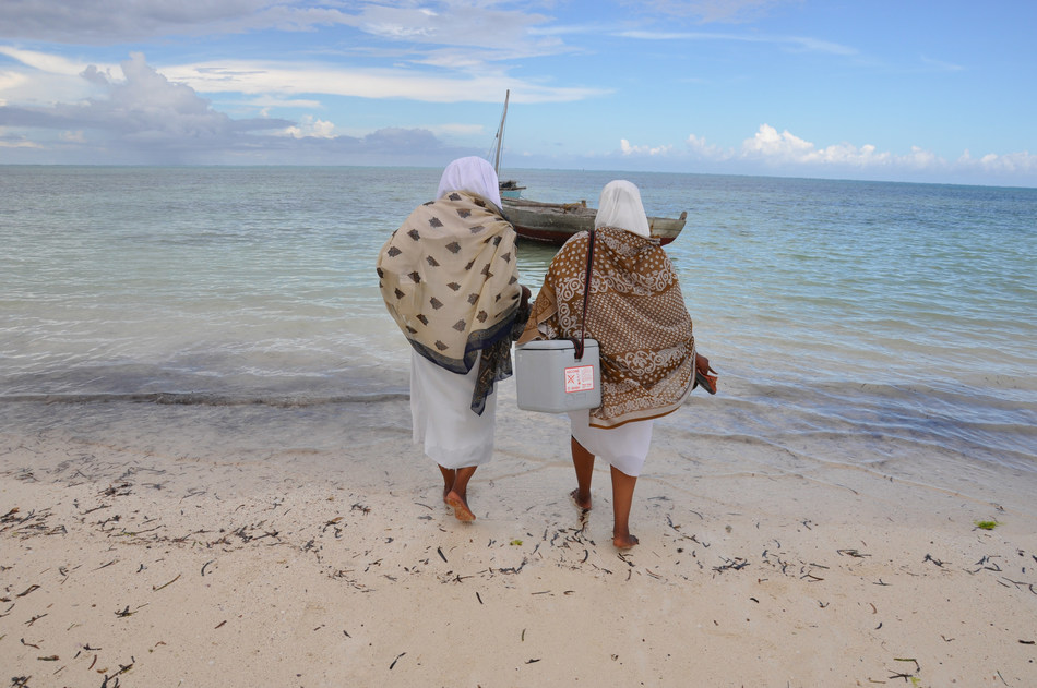 The 'last mile' of vaccine delivery often involves overcoming significant geographic obstacles. In this photo, two health workers are preparing to bring a traditional vaccine carrier onto a boat in order to travel between islands. The new freeze-preventive carrier helps ensure the right temperature in any setting. Photo credit: PATH/Doune Porter. (PRNewsfoto/PATH)
