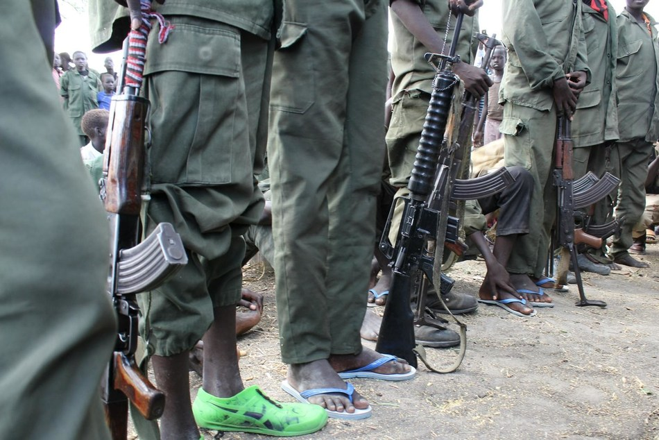 Children queue to hand over their weapons and uniforms during a ceremony formalizing their release from armed groups in South Sudan in 2015. (CNW Group/UNICEF Canada)