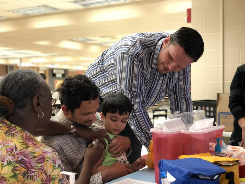 Tony Boselli (right) looks on as a child at the Healthy Schools Emergency Flu Shot Clinic at Mandarin High School receives a flu shot. Healthy Schools vaccinates all kids regardless of insurance status.