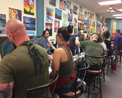 Wounded warriors and their guests utilize their newly learned painting skills to create beautiful pieces of art.