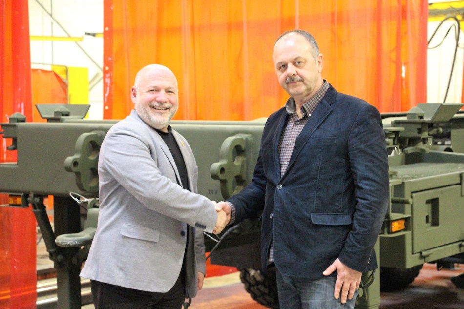 Alain Gautier, Mack Defense (left) and Butch Bouchard, Arne's Welding celebrate the 100th military trailer manufactured at Arne's Welding Ltd. in Winnipeg. (CNW Group/Arne's Welding Ltd.)
