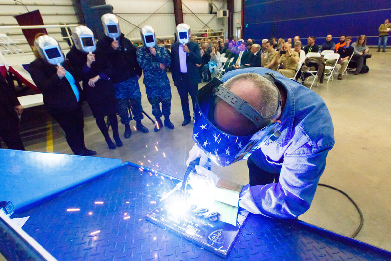 A welder authenticates the keel of LCS 21, the future USS Minneapolis-Saint Paul, by welding the initials of ship sponsor Jodi J. Greene. The Keel Laying is the formal recognition of the start of the ship's module construction process.