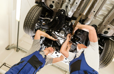 Two car service professionals work under an elevated vehicle