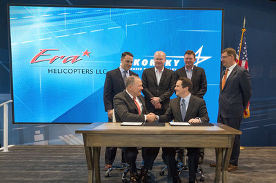 Sikorsky President Dan Schultz (left) and Era Group President and CEO Chris Bradshaw (right) participate in a ceremony at the 2018 Helicopter Association International Heli-Expo to commemorate the delivery of the 300th S-92(r) helicopter.