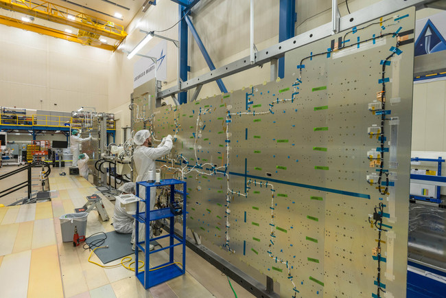Lockheed Martin technicians begin assembly on the JCSAT-17 commercial communications satellite in a clean room near Denver.