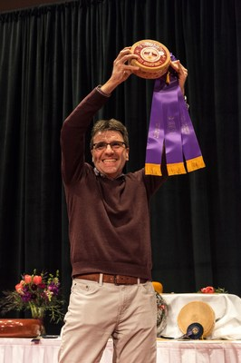 Silvain Diedrichs of Savencia Cheese USA in New Holland, Pennsylvania holds a wheel of Esquirrou, the 2018 World Champion Cheese.  Made by Mauleon Fromagerie in France and imported by Savencia Cheese USA, the hard sheep's milk cheese earned a score of 98.376 out of 100, besting more than 3,400 entries in the record-breaking World Championship Cheese Contest held in Madison, Wisconsin March 6-8.