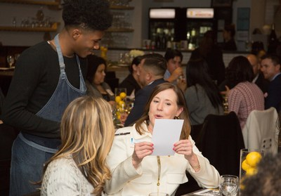 A BBVA Compass guest places her order with a Café Momentum intern Thursday night at the bank's event to celebrate the restaurant's founder, Chad Houser, who won the first-place prize of $50,000 in the BBVA Momentum accelerator program for social entrepreneurs.