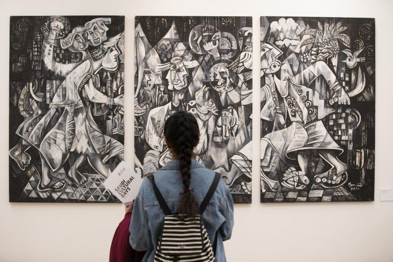 """A visitor stands before an acrylic image by artist Mohammed Siam, renowned for his cubist-style paintings and known as """"the Picasso of Saudi Arabia"""" Credit: David Parry/PA Wire (PRNewsfoto/Gen Culture Auth of Saudi Arabia)"""